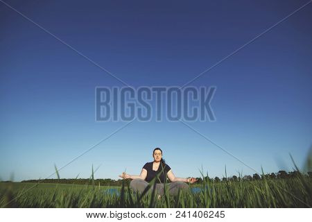 Body Positive, Tranquility, Calm State Of Mind, Meditation, Relax. Overweight Woman Meditating Sitti