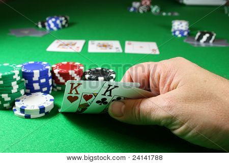 The Game - Pocket Kings, in a poker game ,with the the flopped cards just visible in the background making 4 kings.
