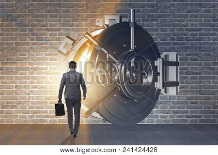 Businessman in front of banking vault door