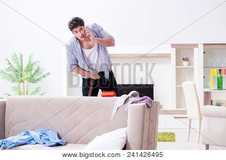 Man with mess at home after house party