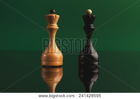 Pair Of Queen Chess Pieces Confronted As Opposites On Green Background With Reflection. Forbidden Lo