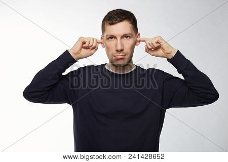 Angry Annoyed Bearded European Man With Compressed Lips Dressed In Dark Blue Denim, Plugging Ears Wi