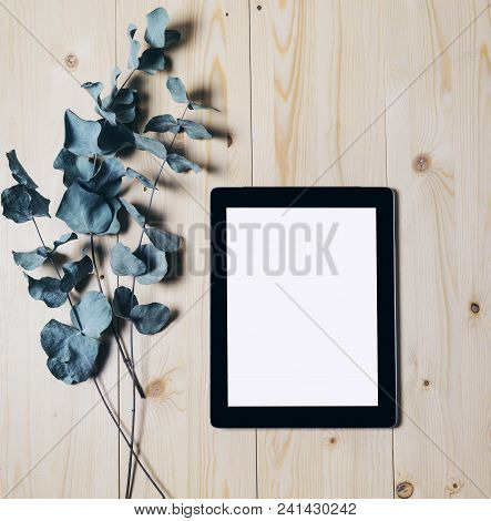 Tablet With A Clean Blank Screen Monitor With A Branch Of Eucalyptus On A Wooden Background With Nat
