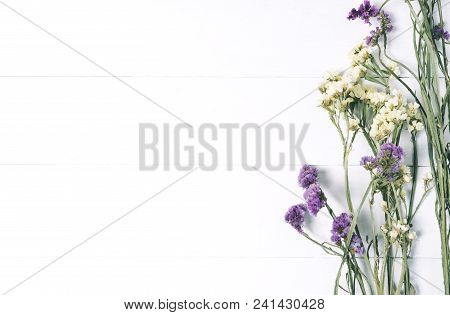 Bouquet Of Dried Wild Flowers On White Table Background  With Natural Wood Vintage Planks Wooden Tex