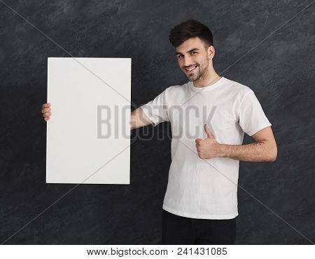 Young Cheerful Man With Blank White Banner And Recommend. Smiling Man Holding Advertising Sheet And