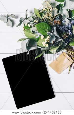 Closeup Tablet With A Empty Blank Screen Monitor With A Bouquet Of Flowers On White Table Background