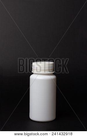 One White Pill Bottle On Black Background. Storage Pills. Vitamins. Release Pills. Vertical