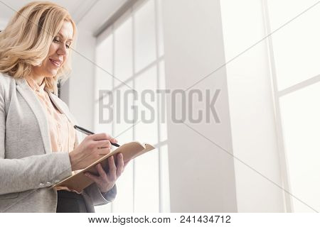 Successful Serious Businesswoman In Formal Wear Reading Book While Standing Near Window, Copy Space,