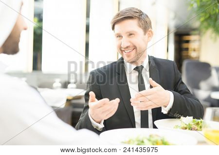 Young smiling businessman in suit having talk to his foreign guest during business lunch in restaurant