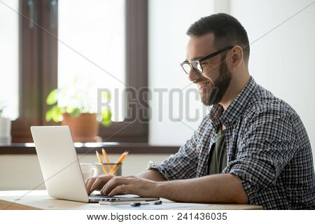 Happy Male Office Worker Smiling Typing Message At Laptop, Chatting With Friends, Writing Positive E
