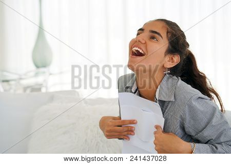 Young Woman Enjoying Good News In Writing. The Girl Reads A Letter With Good News Sitting On The Cou