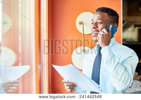 Happy young agent in formalwear talking by smartphone while looking through window of his office