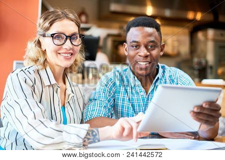 Happy intercultural brokers in formalwear looking at camera while searching for online information about financial development
