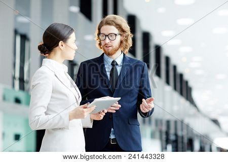 Young confident broker explaining his colleague statistic data during meeting in airport lounge before departure