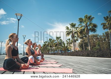 Full Length Side View Calm Ladies Meditating On Mats At Seafront. Peace In Soul Concept