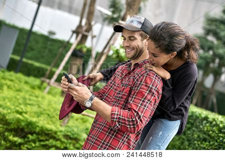 Charming interracial couple is posing outdoors. Smiling white guy in a red shirt holds a smartphone and his black girlfriend hugs him from behind. She holds a crimson hat. Horizontal. poster
