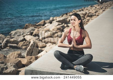 Full Length Portrait Of Happy Female Expressing Calmness While Sitting In Lotus Pose Over Coast. Pea