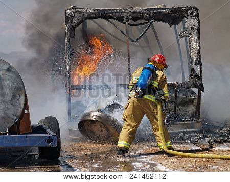 A Firefighter Battling To Put Out An Intense Fire Of A Burning Recreational Vehicle In Arizona. The