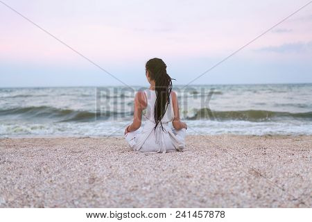 Woman With Dreadlocks Practices Yoga And Meditates In The Lotus Position On The Beach