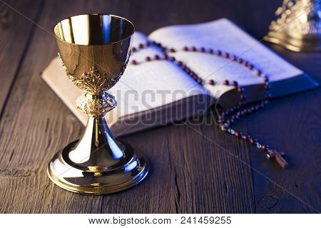 Roman Catholic Church Theme. The Cross, Holy Bible, Rosary And Golden Chalice.