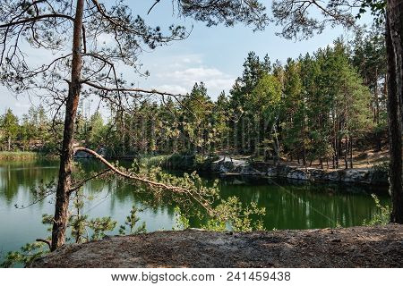 Picturesque Landscape With A Lake In The Middle Of A Coniferous Forest In Korostyshiv Quarry, Zhytom