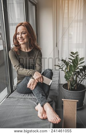 Full Length Portrait Of Happy Woman Relaxing By Her Window At Home. She Is Enjoying Herself In Pleas