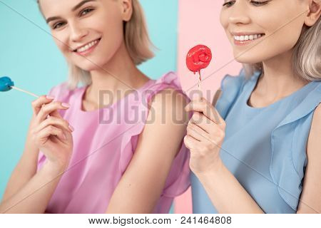 Young Girls In Summer Garment Enjoying Candies. Focus On One Woman