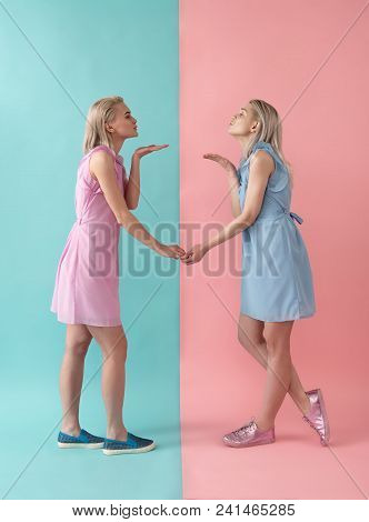 Side View Profile Of Pretty Girls In Dresses Holding Hands And Sending Air Kisses One Another