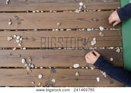 Top View Of Child's Hands Playing With Stones