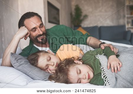 Portrait Of Beaming Dad Hugging Calm Sons While They Sleeping In Bed