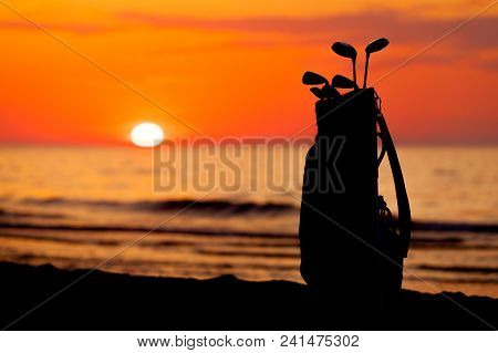 Idyllic Shot Of Sunset By The Sea Waters, Warm, Orange And Red Colors And Bag With Golf Club Equipme