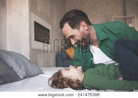 Side View Happy Father Lying Near Outgoing Child. They Talking Together In Room