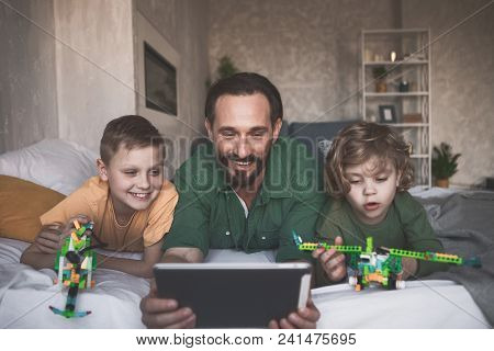 Portrait Of Outgoing Brothers And Satisfied Dad Looking At Electronic Tablet While Relaxing On Bed
