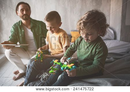 Portrait Of Cheerful Children Sitting Near Happy Father. They Having Fun Together