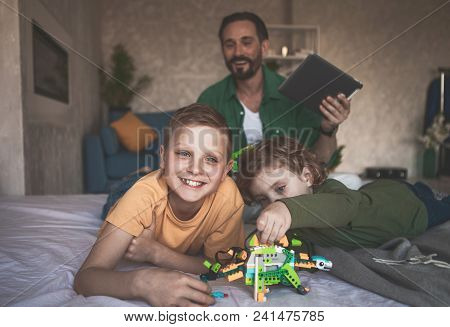 Portrait Of Happy Kids Playing With Outgoing Dad In Toys. He Keeping Gadget In Arm