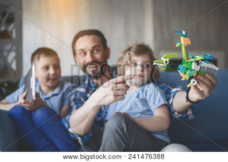 Portrait Of Outgoing Dad Showing Robot For Concentrated Kids. They Sitting In Apartment. Happy Famil