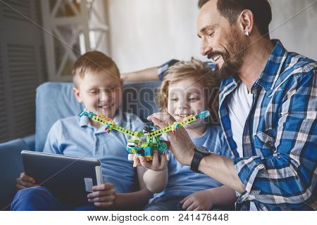 Outgoing Dad Having Fun With Satisfied Children. They Looking At Toy. Glad Boy Typing In Gadget