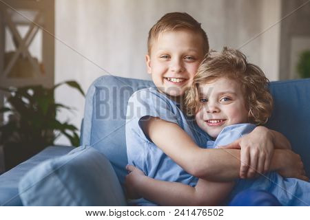 Portrait Of Two Outgoing Children Hugging Each Other While Looking At Camera
