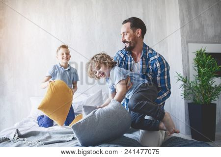 Glad Bearded Father Playing With Cheerful Kids. He Holding Small Boy In Hands. Happy Parent And Chil