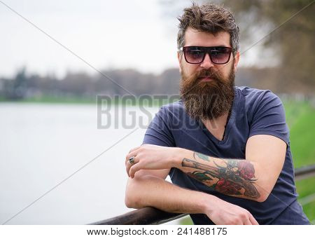 Man With Beard And Mustache Wears Sunglasses, River Embankment On Background. Hipster On Confident F