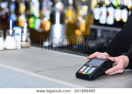 Electronic Finance And Shopping Concept. Cashiers Hand Holds Credit Card Reader On Defocused Backgro