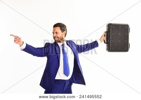 Businessman Raises Up Briefcase Above His Head And Points To Opposite Side With Index Finger. Man In