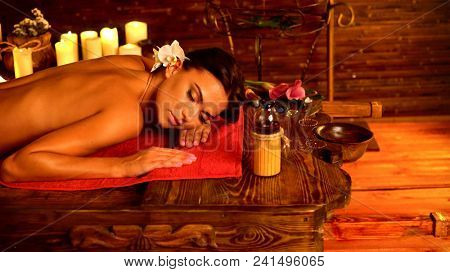 Massage of woman in spa salon. Girl on candles background in massage spa salon. Luxary interior in oriental therapy salon. Female have relax after sport. Spa salon is corner of silence and tranquility