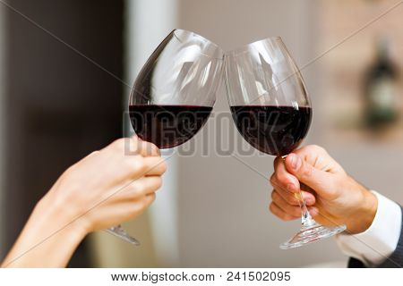 Closeup of a couple toasting wine glasses