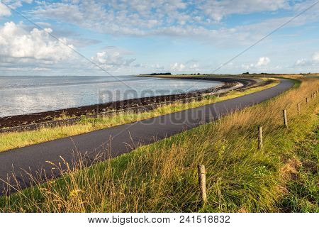 Curved Asphalt Road On A Dike Along The Water Of A Dutch Estuary. It Is Low Tide On A Sunny Day In T