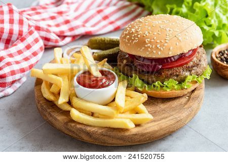 Homemade Beef Burger And French Fries With Ketchup On Wooden Board On Gray Concrete Background. Hori
