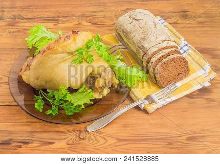 Baked Ham Hock With Greens On A Dark Glass Dish, Partly Sliced Brown Bread And Fork On Checkered Nap