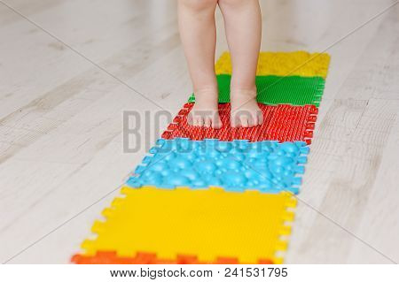 Legs Of The Child, The Kid Go On Massage Mats. Exercises For Legs On Orthopedic Massage Carpet. Orth