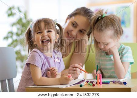 Female Teacher Working With Children In Preschool Classroom