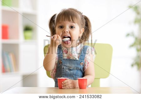 Cute Little Child Girl Eating Yogurt Indoors